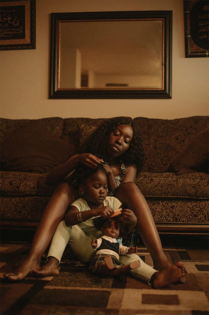 Una madre afrodescendiente peina el cabello a su hija.