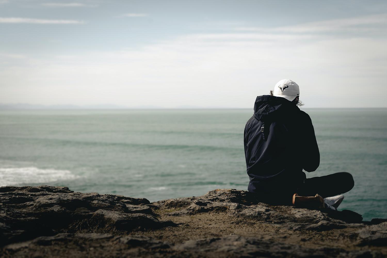 Un chico mira al horizonte en el mar.